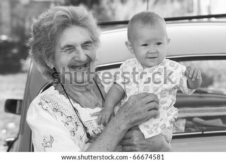 The old grandmother holds the little grand daughter and smiles. Shallow DOF. - stock photo