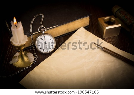 The old handle feather and a sheet of paper with a candle - stock photo