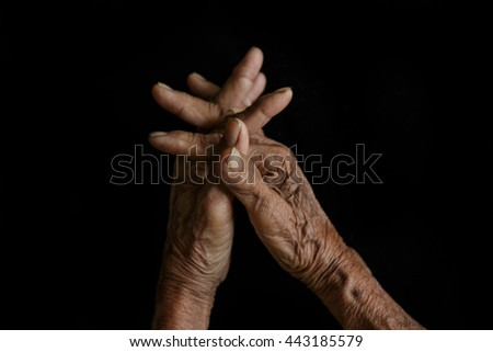 The old hands grandmother in a black background - stock photo