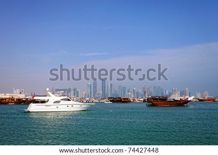 The old harbour in Doha, Qatar, with dhows and a luxury yacht. The high-rise skyline of the new business district is in the background. Shot in January 2011. - stock photo