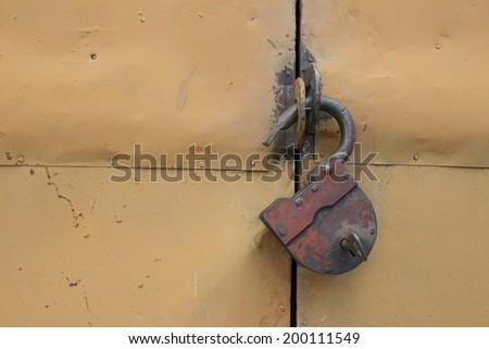 The old hinged granary rusty lock on orange doors - stock photo