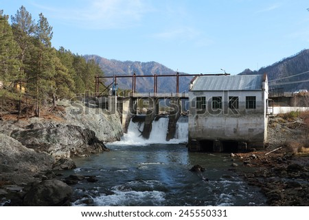 The old hydroelectric power station on the river Chemal after a flood in mountain Altai in Russia - stock photo