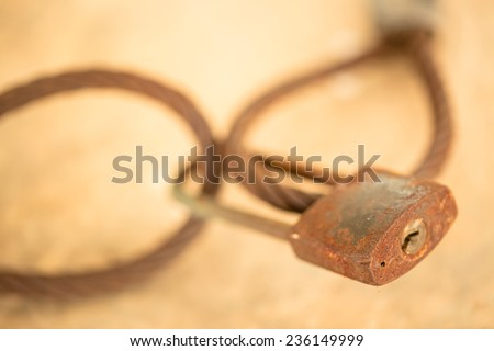 The old key locked on rusty sling - stock photo