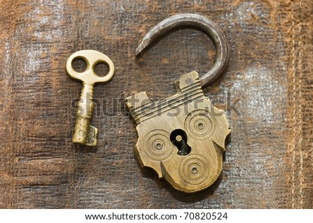 The old lock and key on a leather background - stock photo