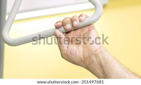 The old man hand holding on the triangle above the hospital bed.  - stock photo