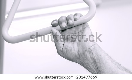 The old man hand holding on the triangle above the hospital bed. Black and white. - stock photo