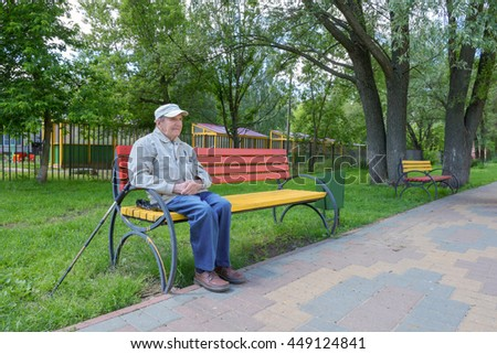 The old man in cap poses on a park bench in summer