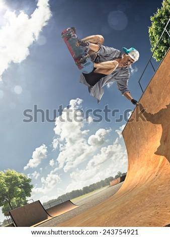 The old man is skating on skateboard in skate park - stock photo