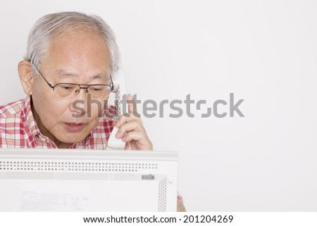 The old man talking on the phone while operating the laptop