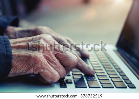The old man typing with laptop in morning light.vintage effect - stock photo
