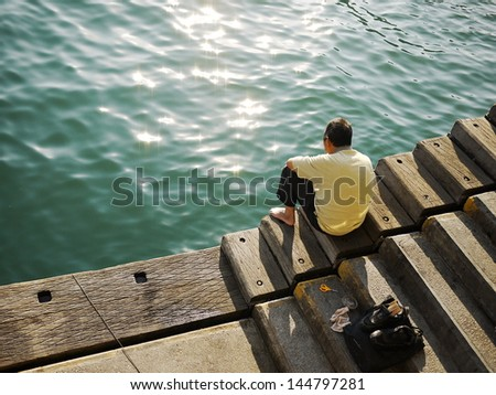 the old man watch the sea during the fishing in Sai Kung harbor, Hong Kong, China - stock photo