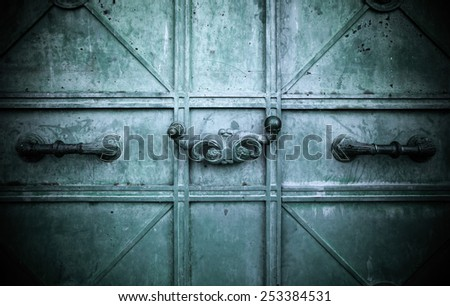 The old metal door with curly handles. Background. Toned.