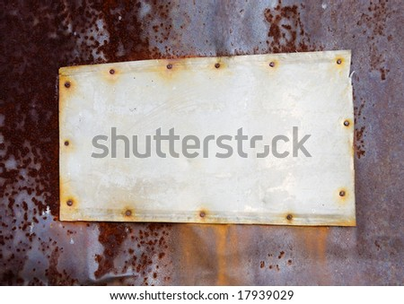 The old metal tablet on a rusty wall - stock photo