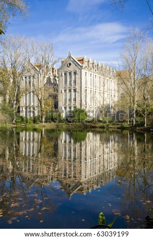 The old military headquarters and high school college building reflected over the lake at Parque D. Carlos I, in Caldas da Rainha, Silver Coast, Portugal - stock photo