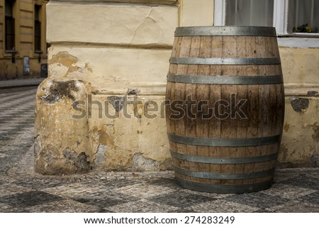 The old oak wine barrel, metal rims with rust, barrel standing on the street. - stock photo