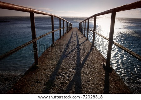 The old pier on the beach - stock photo