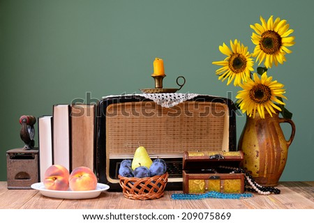 The old radio, sunflower and books on the table - stock photo