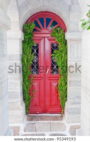 The old red door of the church, surrounded by marble and green branches of laurel - stock photo