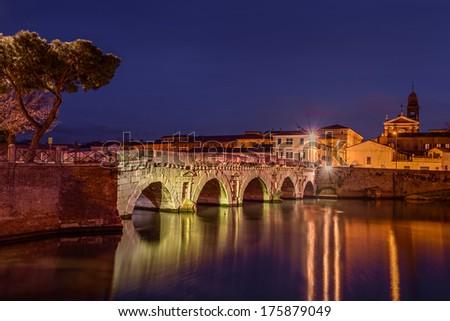 the old roman bridge of Tiberius at night in Rimini, ancient landmark of Italy  - stock photo