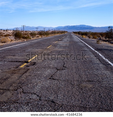The old Route 66 with damaged pavement in the Mohave desert, California,U.S.A. - stock photo