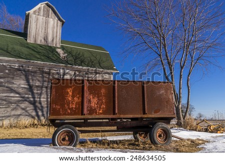 The old rusted metal wagon with vintage wooden barn in the beautiful late afternoon light near Rochelle, Illinois, USA. - stock photo