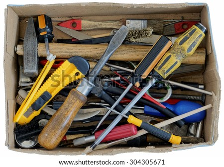 The old rusty used tools of the grandfather lie in a fragmentary cardboard box. Isolated with patch