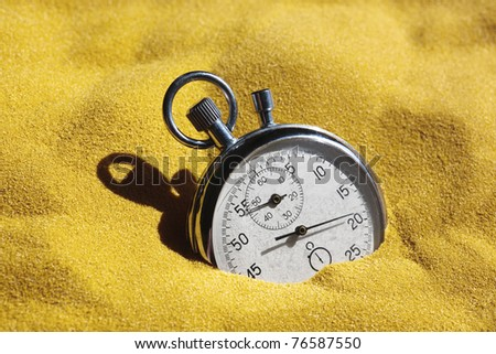 The old scratched stopwatch in yellow sand is covered by the sun. A metaphor of time. - stock photo