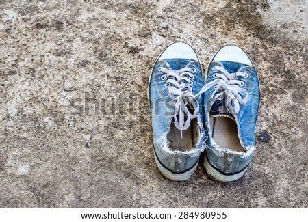 The Old sneakers shoe on the floor - stock photo