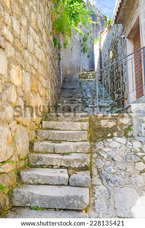 The old stone stairs on the hilly street and the high wall, going to the top, Perast, Montenegro. - stock photo