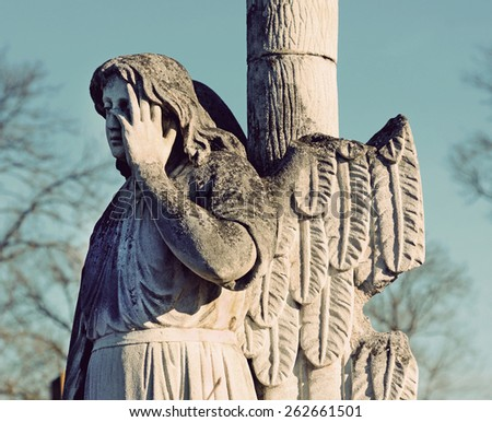 The old stone statue of an angel headstone in the cemetery in vintage style - stock photo