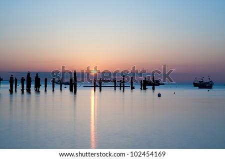 The old  Swanage Pier at sunrise - Dorset, UK - stock photo