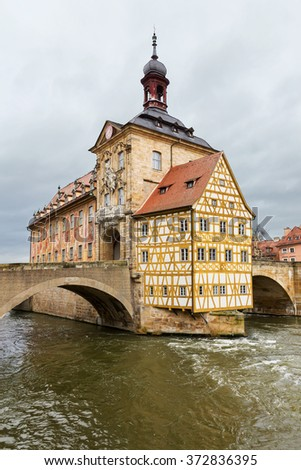 The old Town Hall in Bamberg built in the middle of the river Regnitz, in Upper Franconia, Bavaria, Germany, with facade covered with colourful frescoes. - stock photo