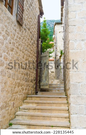 The old town located at the foot of the mountain, so there are many narrow streets with the old staircases, going up, Perast, Montenegro. - stock photo