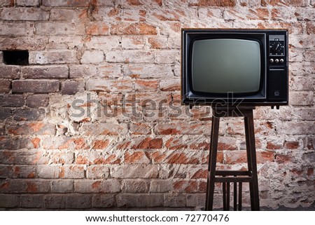 The old TV set against an old brick wall - stock photo
