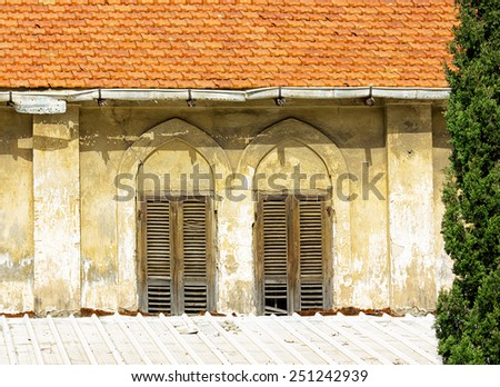 The old windows  with wooden shutters on a yellow wall. Vintage background -texture. - stock photo
