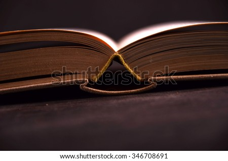 The old, wise book lies on a wooden back - stock photo