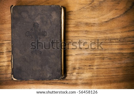 The old, wise book lies on a wooden background - stock photo