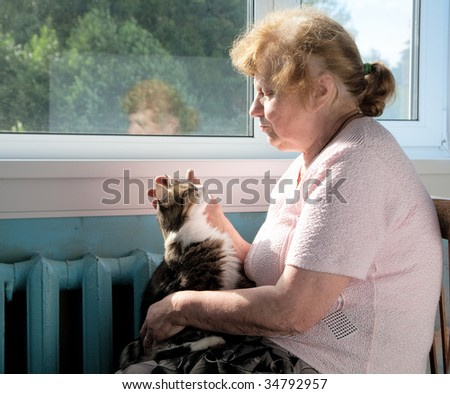The old woman caress cat sitting at a window - stock photo