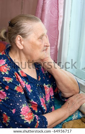 The old woman looks out of the window - stock photo