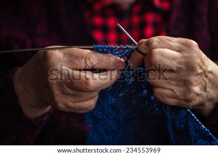 The old woman sits at home and knits garments. Close up. - stock photo