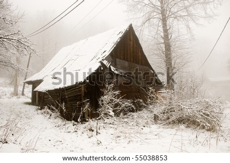 The old wooden cottage covered by white snow - stock photo