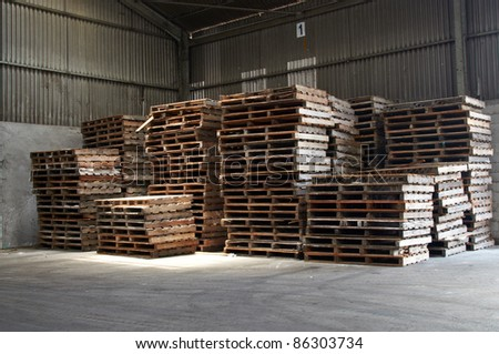 the old wooden pallets stacked at warehouse - stock photo