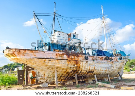 The old wooden ship located on the seashore next to the village entrance, Latchi, Cyprus. - stock photo