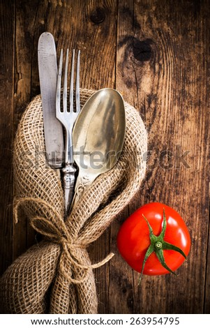 The old wooden table cutlery, and tomatoes. - stock photo