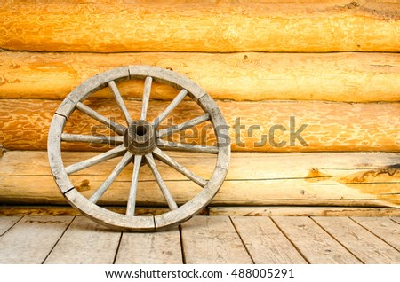The old wooden wheel near the wooden wall.