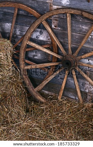 The old wooden wheel on a hay - stock photo