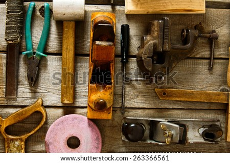 The old working tool. Many old working tools ( plane, saw, pliers and others) on a wooden background. - stock photo