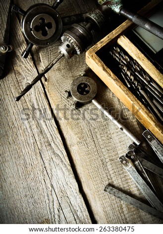 The old working tool. Old drill, a box with drills, pliers and ruler on wooden background. - stock photo