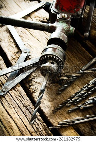 The old working tool. Old drill, a ruler and drills on a wooden background. - stock photo