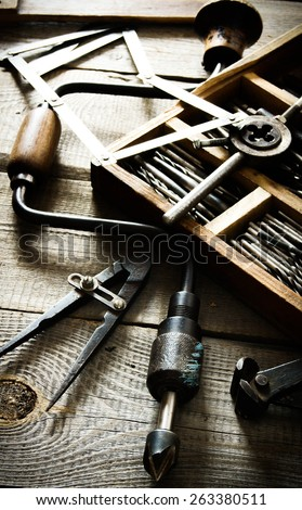 The old working tool. Old drill, compasses, ruler and compasses on a wooden background. - stock photo